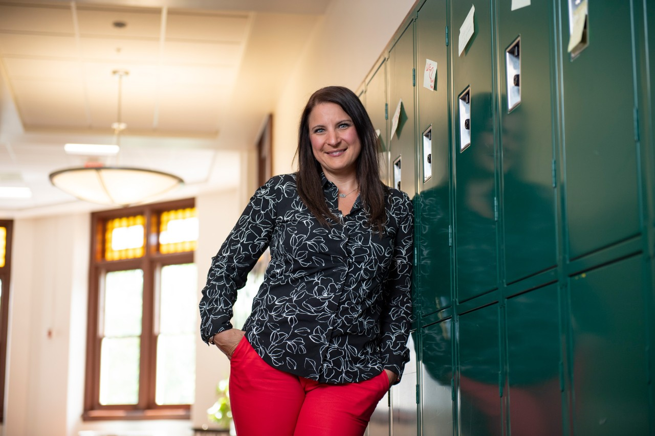 Jennifer Wright-Berryman, an assistant professor in the School of Social Work, leans against a bank of lockers in a hallway