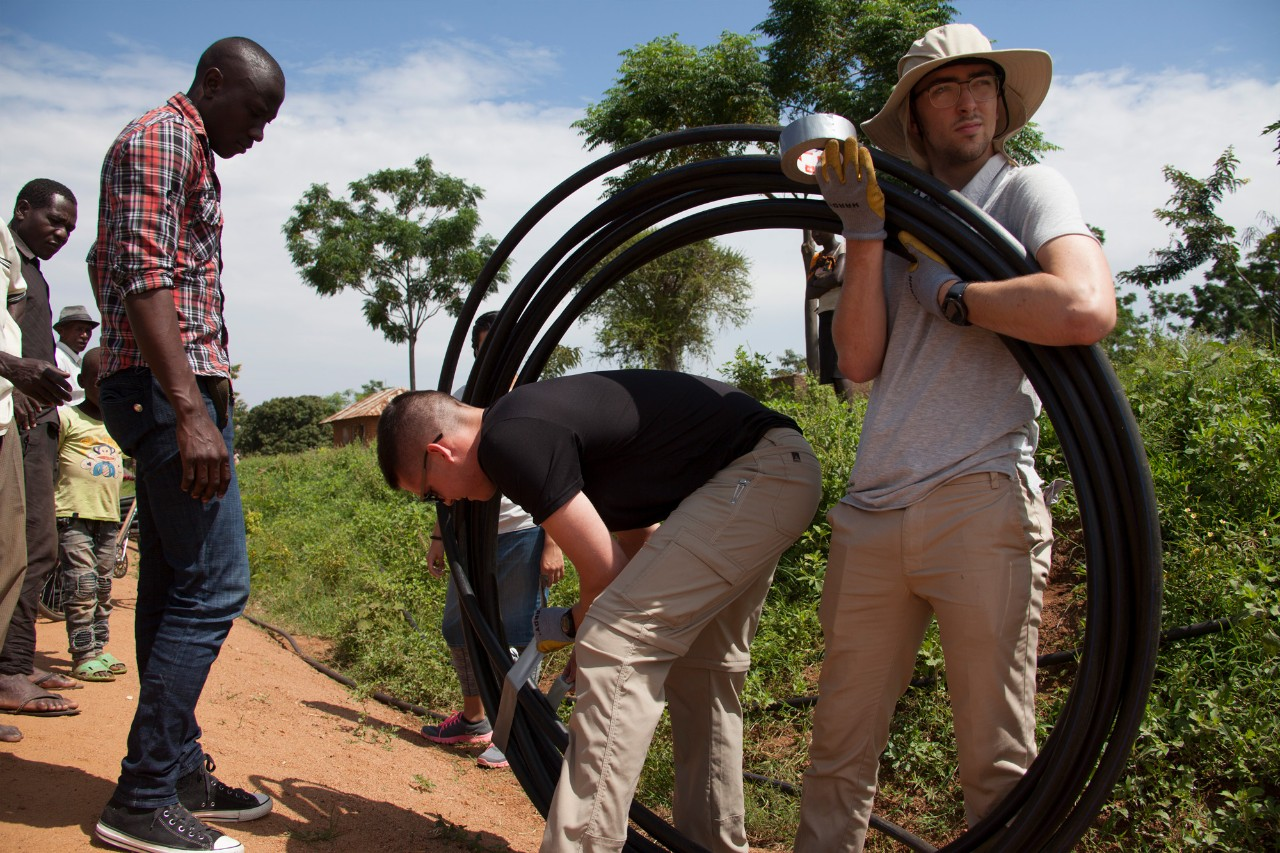 UC's Engineers Without Borders work on a water project in Tanzania while carrying pipe