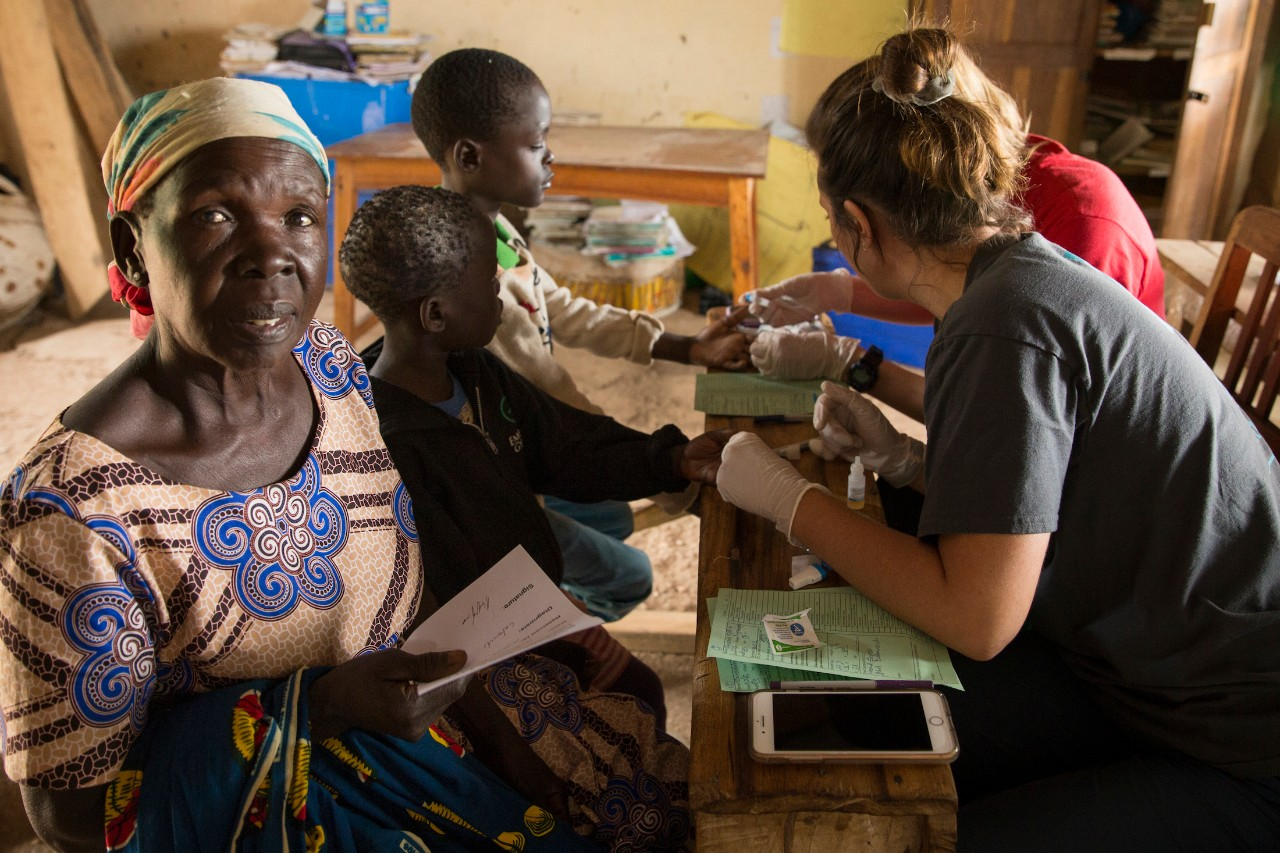 A grandmother sits with her grandchildren while they receive free care at a clinic in Tanzania