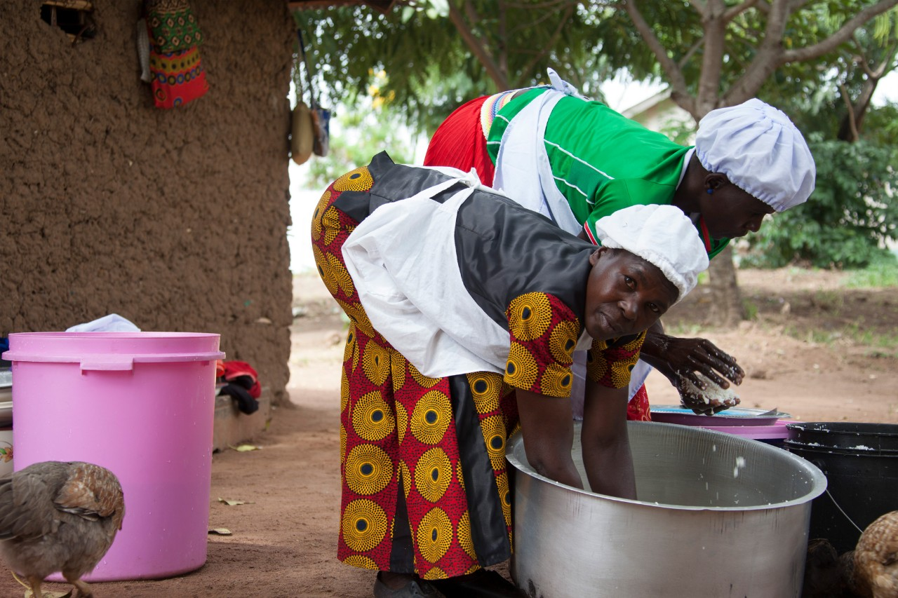 A Tanzanian women stirs rice in a large pot with her hands