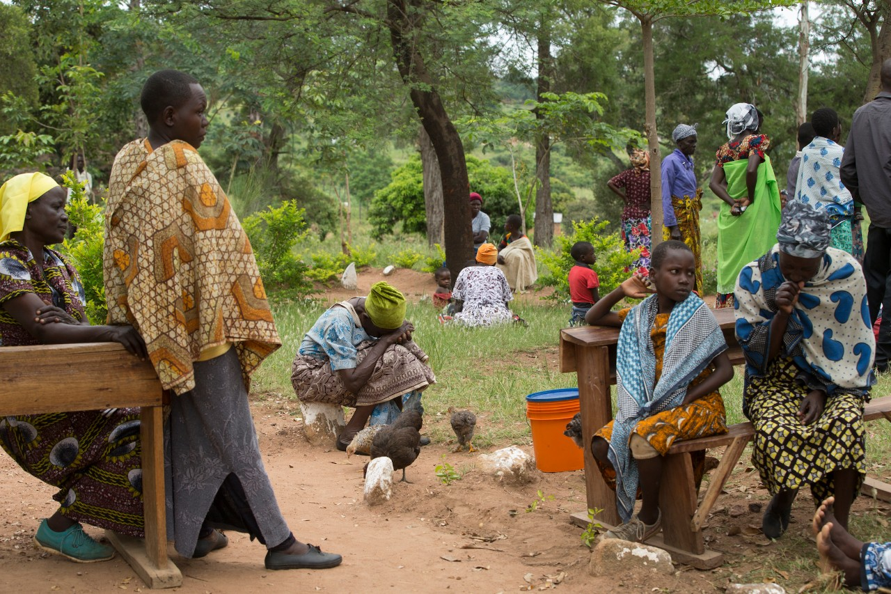 Patients sit on ground outside a clinic waiting to be seen by doctors in Tanzania