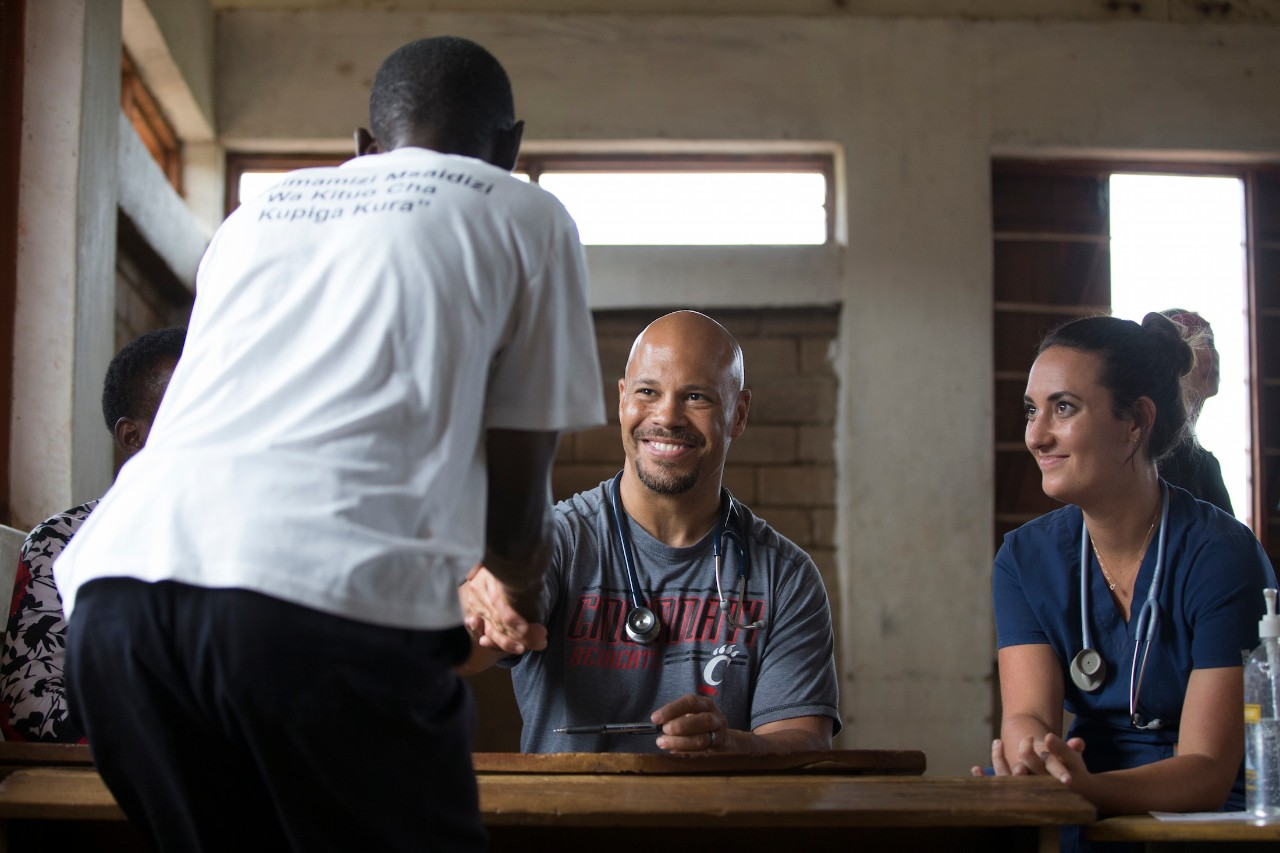 Chris Lewis and a volunteer meet with a patient in a clinic in Tanzania