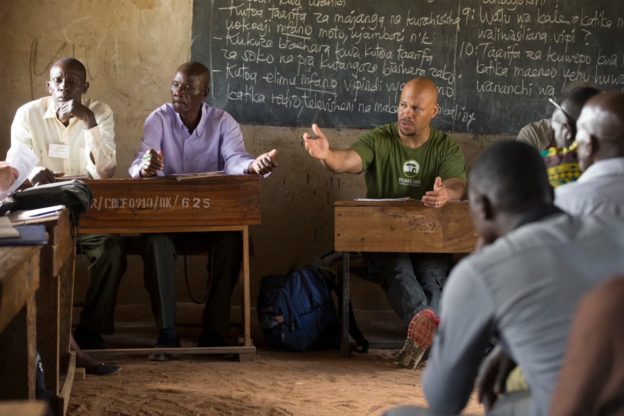 A meeting at Burere Village in Tanzania shows Chris Lewis leading a discussion