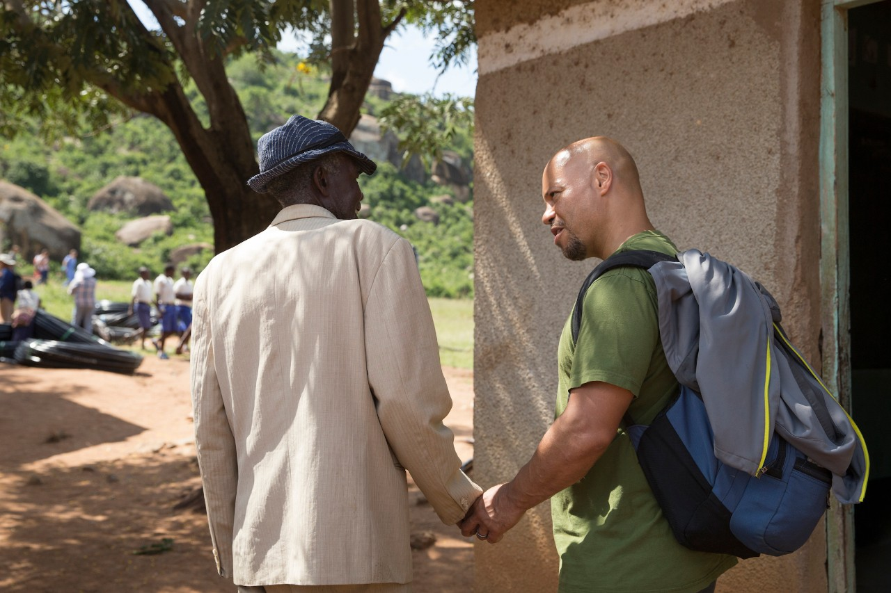 Chris Lewis holds hands with a villager in Tanzania