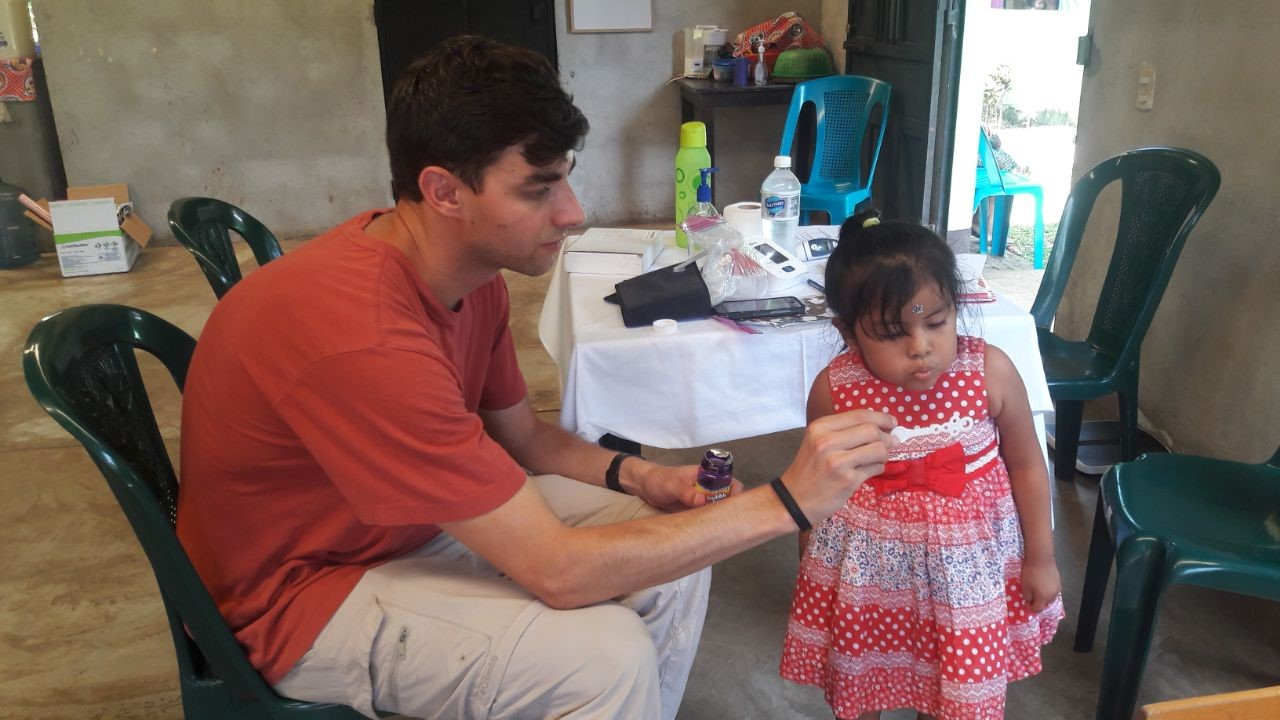 UC graduate student blowing bubbles with a child  in a Guatemalan medical clinic.
