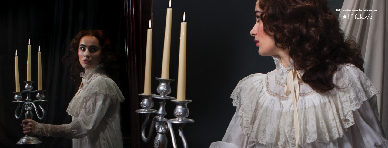 Woman in a nightgown holds a candelabra and looks into a mirror