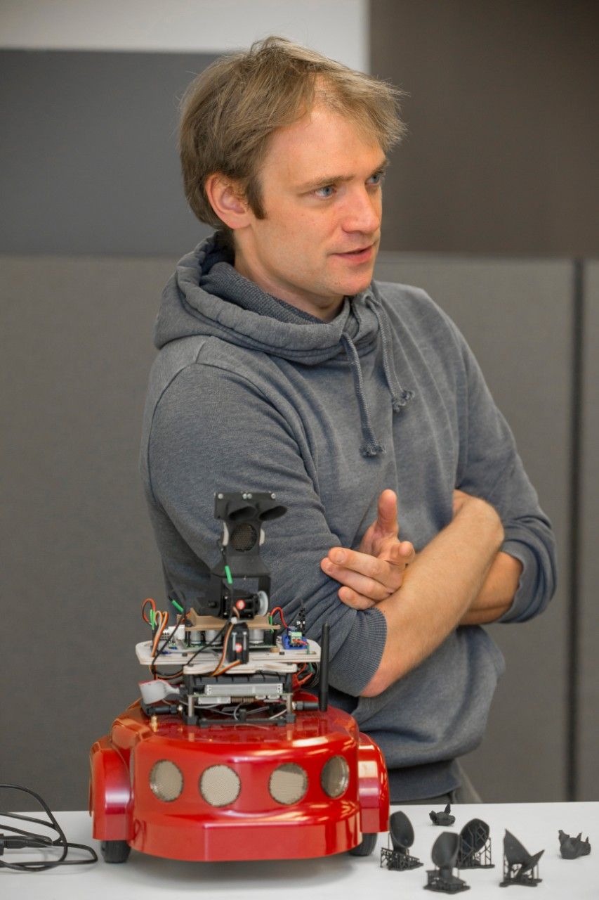 UC engineering professor Dieter Vanderelst stands in front of a table upon which is his custom-built bat-inspired robot.