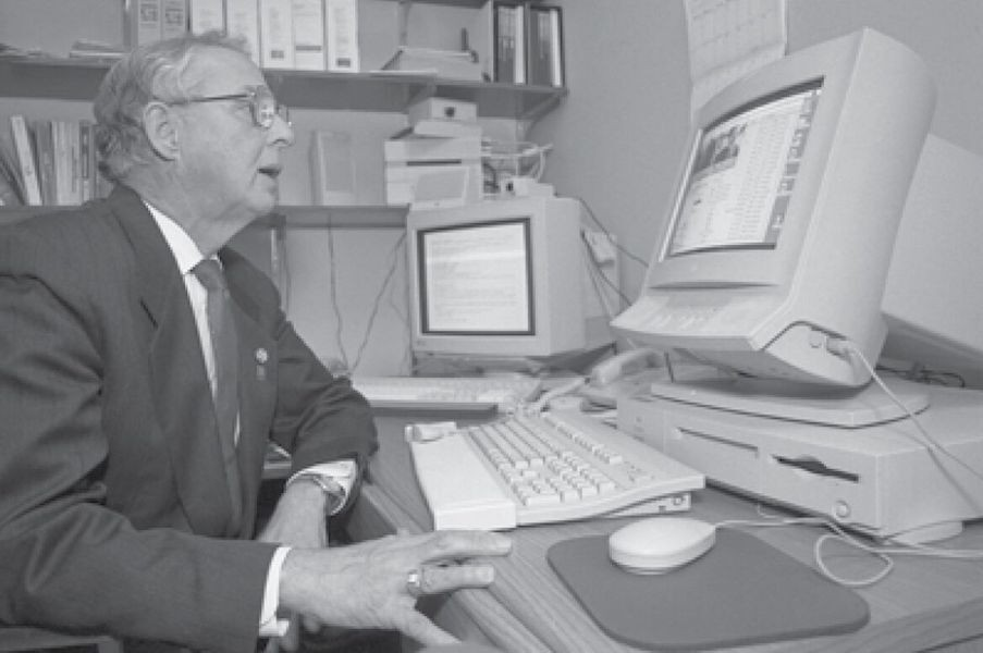 Black and white photo of a man on a computer