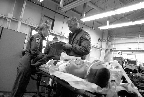 Black and white photo of trauma care team working on a medical dummy