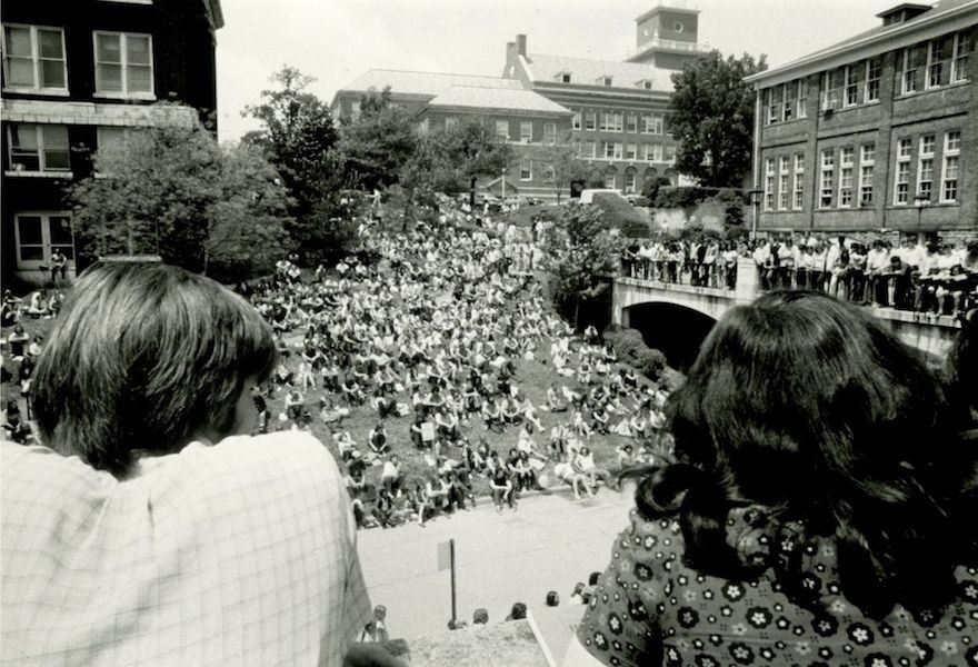 Black and white photo of the backs of two heads looking onto a lawn and bridge filled with students