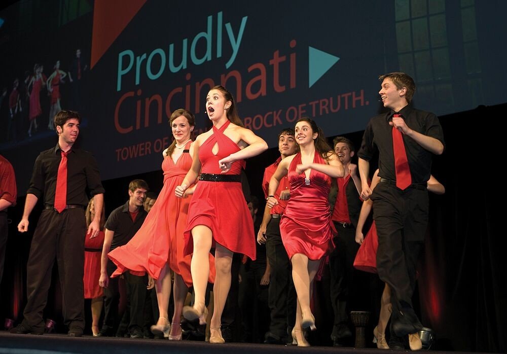 Students sing and dance onstage in front of a Proudly Cincinnati sign