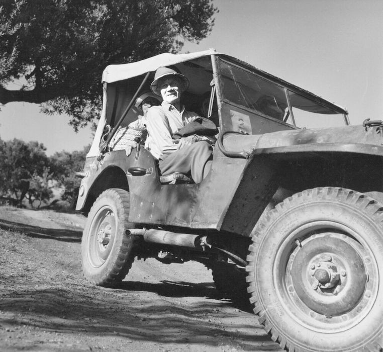 Black and white photo of a man in a Jeep rover