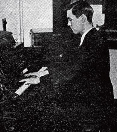 Black and white photo of a man playing organ