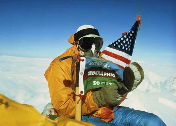 Climber at the top of Mount Everest holding American flag