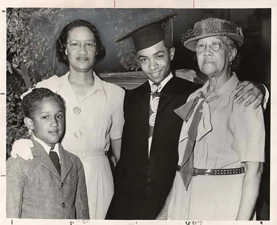 Black and white photo of a graduate in cap and gown, his mother, grandmother and little brother