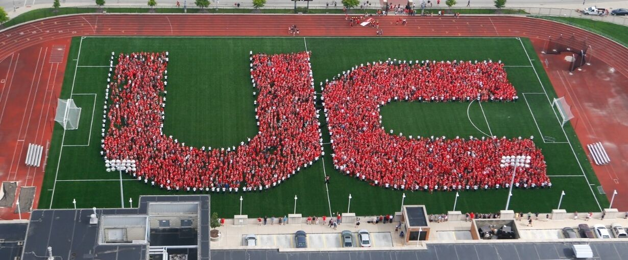 """Students  in red gather on a soccer field forming """"UC"""" from above"""