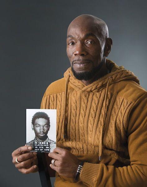 Ohio Innocence Project exoneree holding a photo of his mugshot