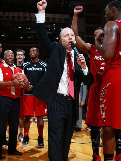 Coach Mick Cronin speaks on a microphone with hand raised around basketball players on court