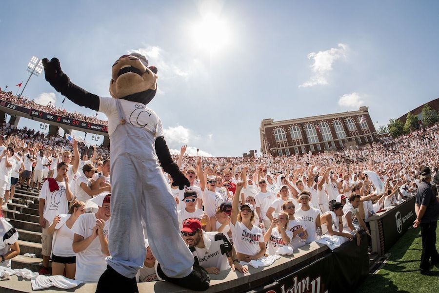 Bearcat mascot in white overalls poses in front of a crowd wearing white