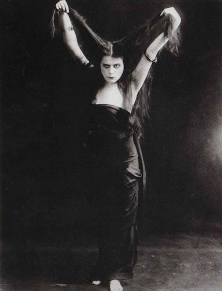 Actress Theda Bara holding her long hair up above her head