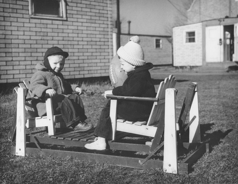 Black and white photo of two young children playing with a football