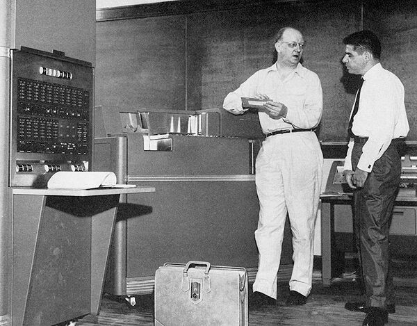 Black and white photo of two men beside UC's first computer
