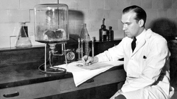 Black and white photo of a man in white lab coat sitting at desk