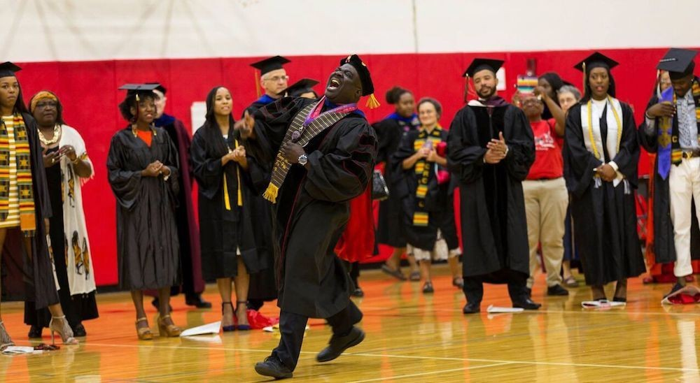 Man in black cap and gown sings in front of a line of graduates