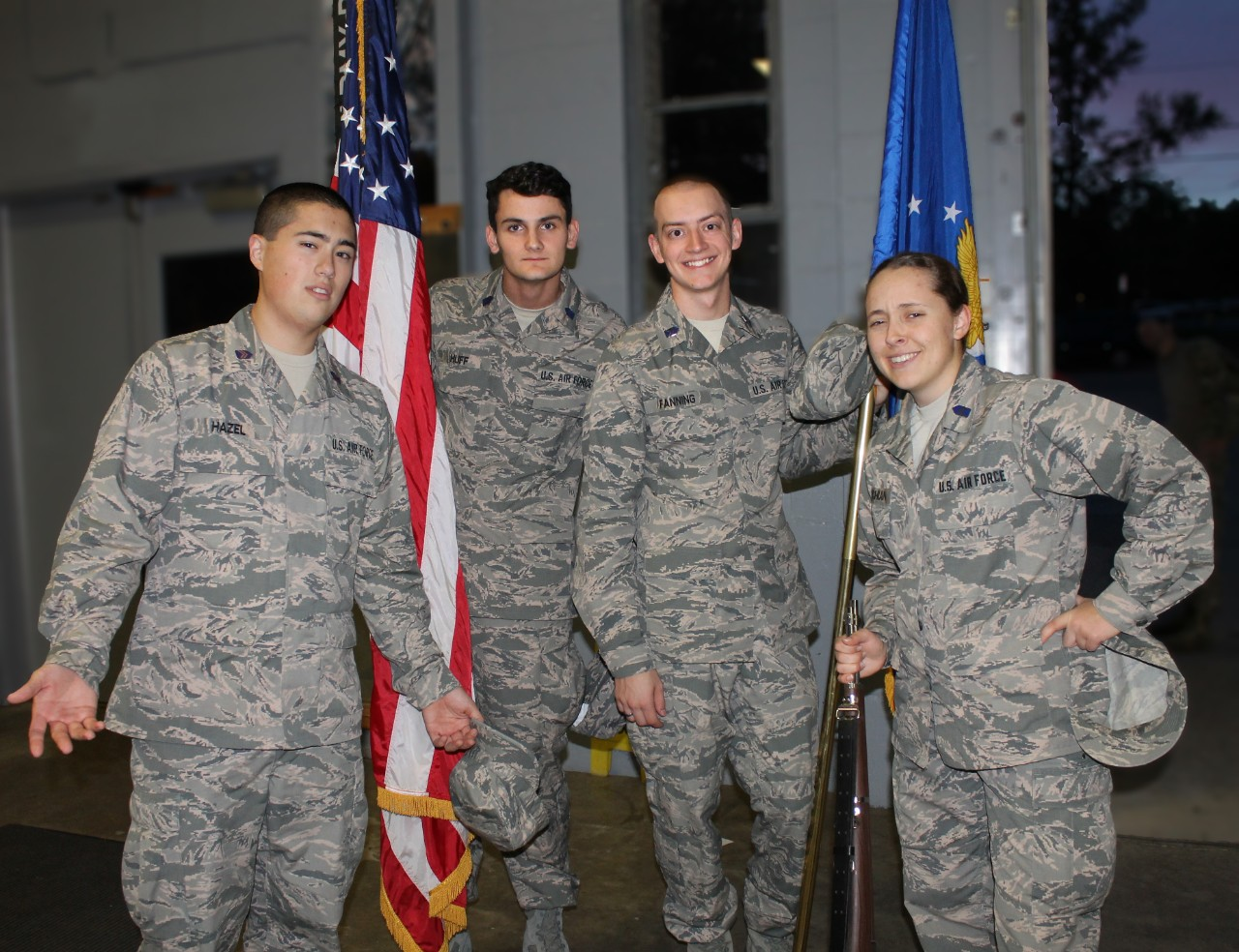 Fanning and three ROTC cadets posing with American flag, all in military camoflage attire.
