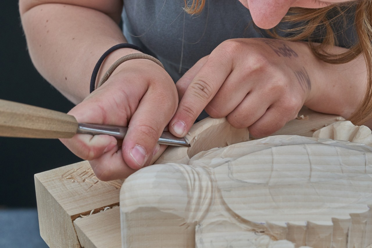 a close-up of a pair of hands carving wood.