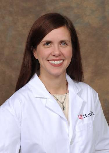 Dr.  Jaime Lewis, a UC Health physician in a white lab coat.