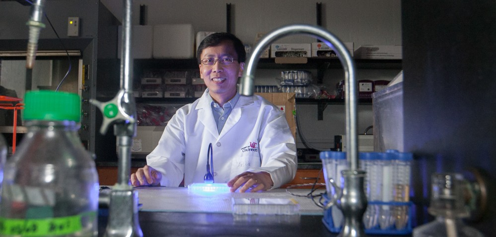 UC chemist Peng Zhang in a labcoat stands  in the dark at his lab bench illuminated by the glow of a blue LED.