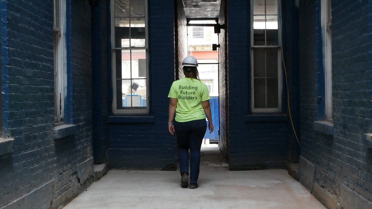 wide shot Swisher with back toward camera on job site in the interior of a historical building.