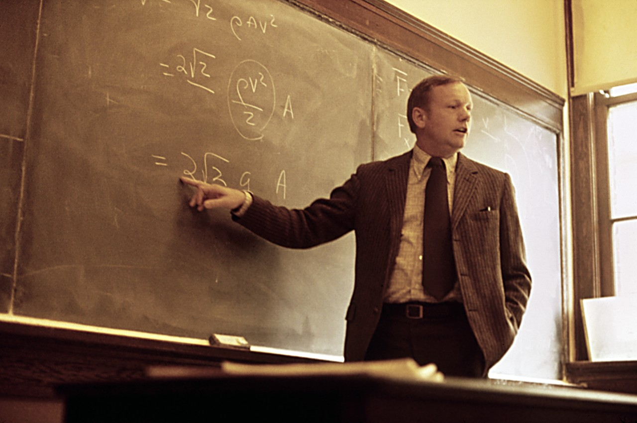 UC professor Neil Armstrong lectures at a blackboard full of equations.