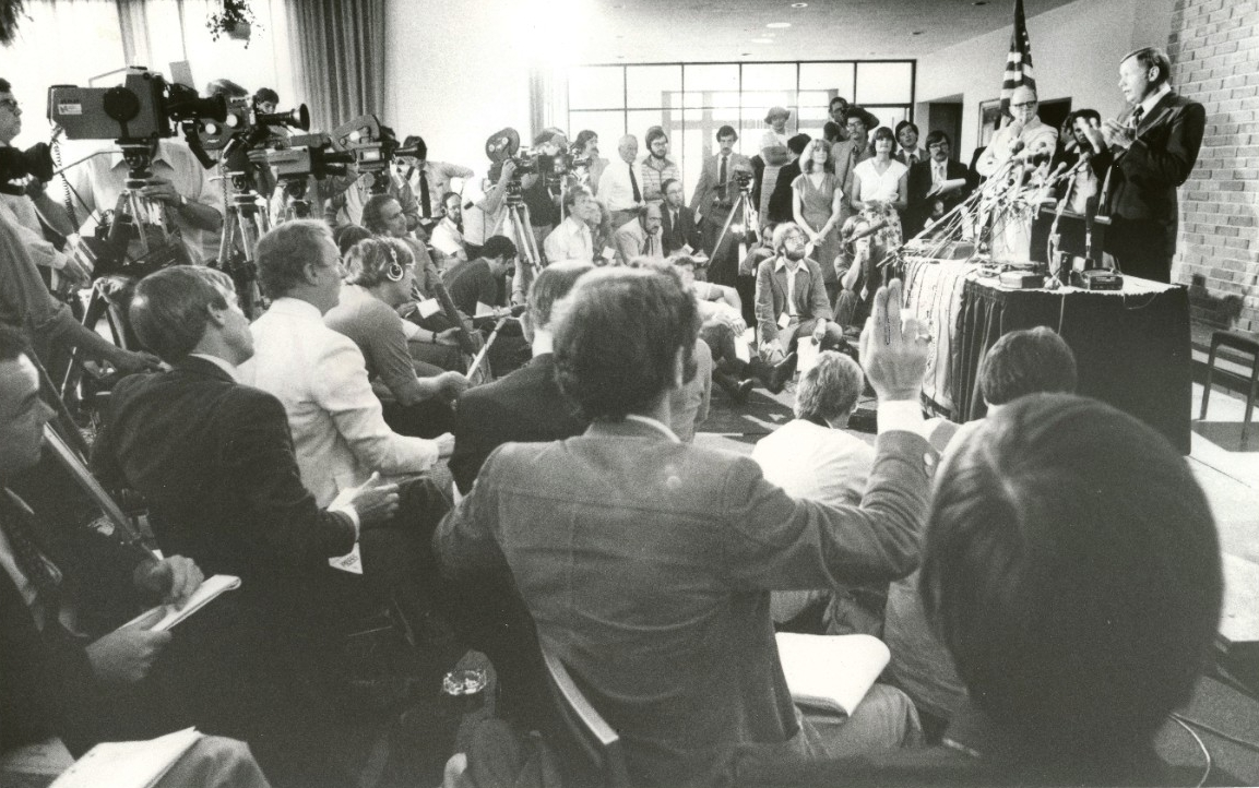Dozens of news cameras crowd around Neil Armstrong at a podium announcing his decision to teach at UC.