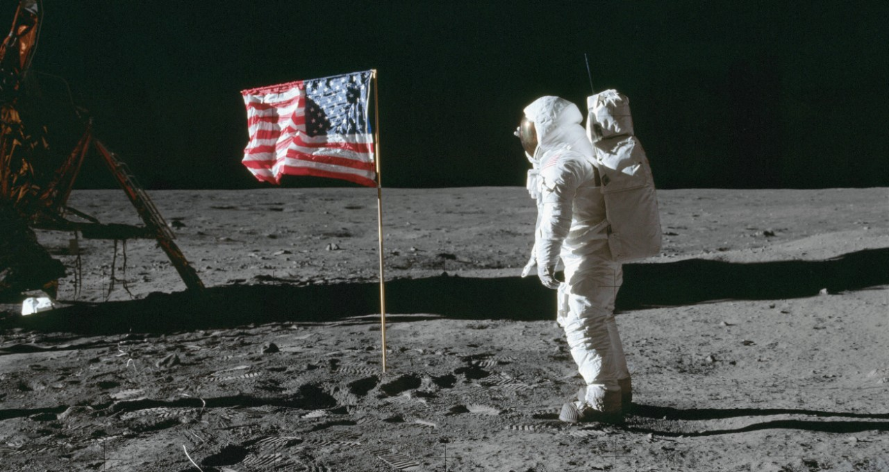 Astronaut Buzz Aldrin stands on the moon in his spacesuit next to an American flag.