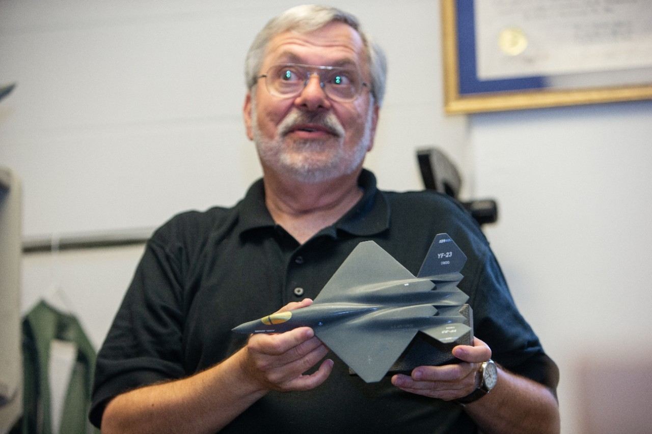 """George """"Tom"""" Black holds a plastic model of an F-22 in his UC engineering office."""