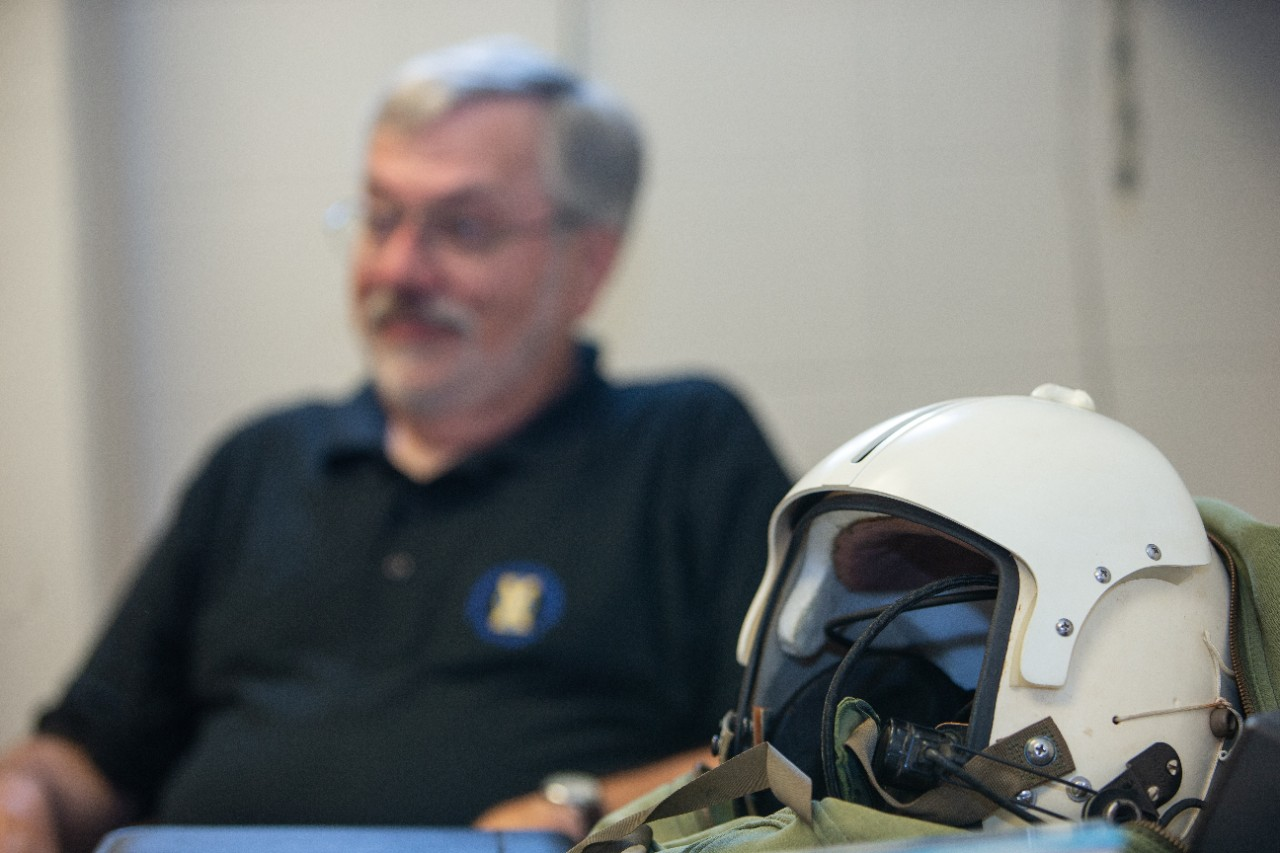 "A white flight helmet in the foreground sits on a desk with George ""Tom"" Black off-focus in the background."