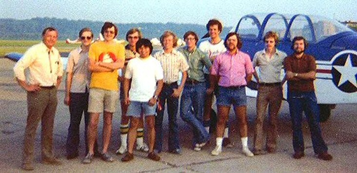 Neil Armstrong and 10 of his engineering students pose in front of a jet on an airport tarmac.