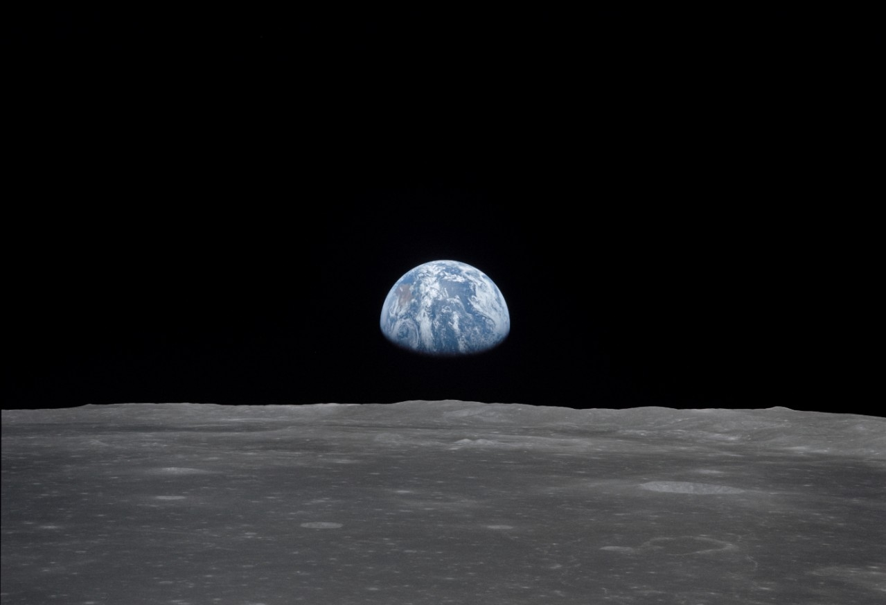 "The ""blue planet"" Earth stands in contrast as it rises over the distant horizon of the barren moon."