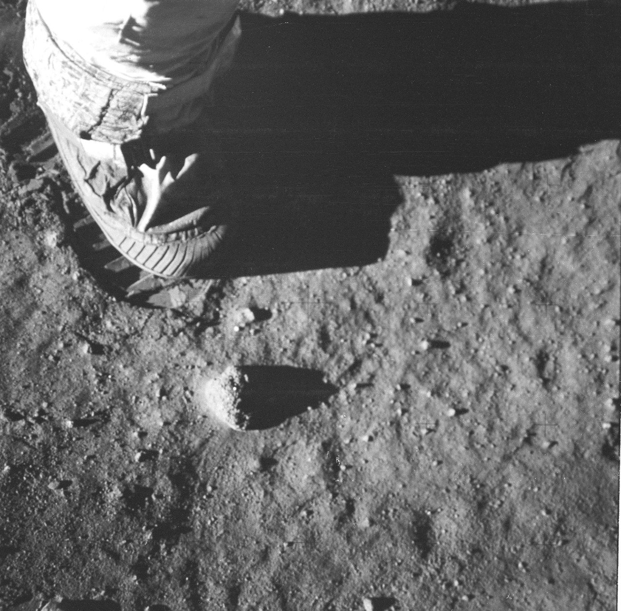 A black and white image of a spacesuit boot next to its footprint on the moon.