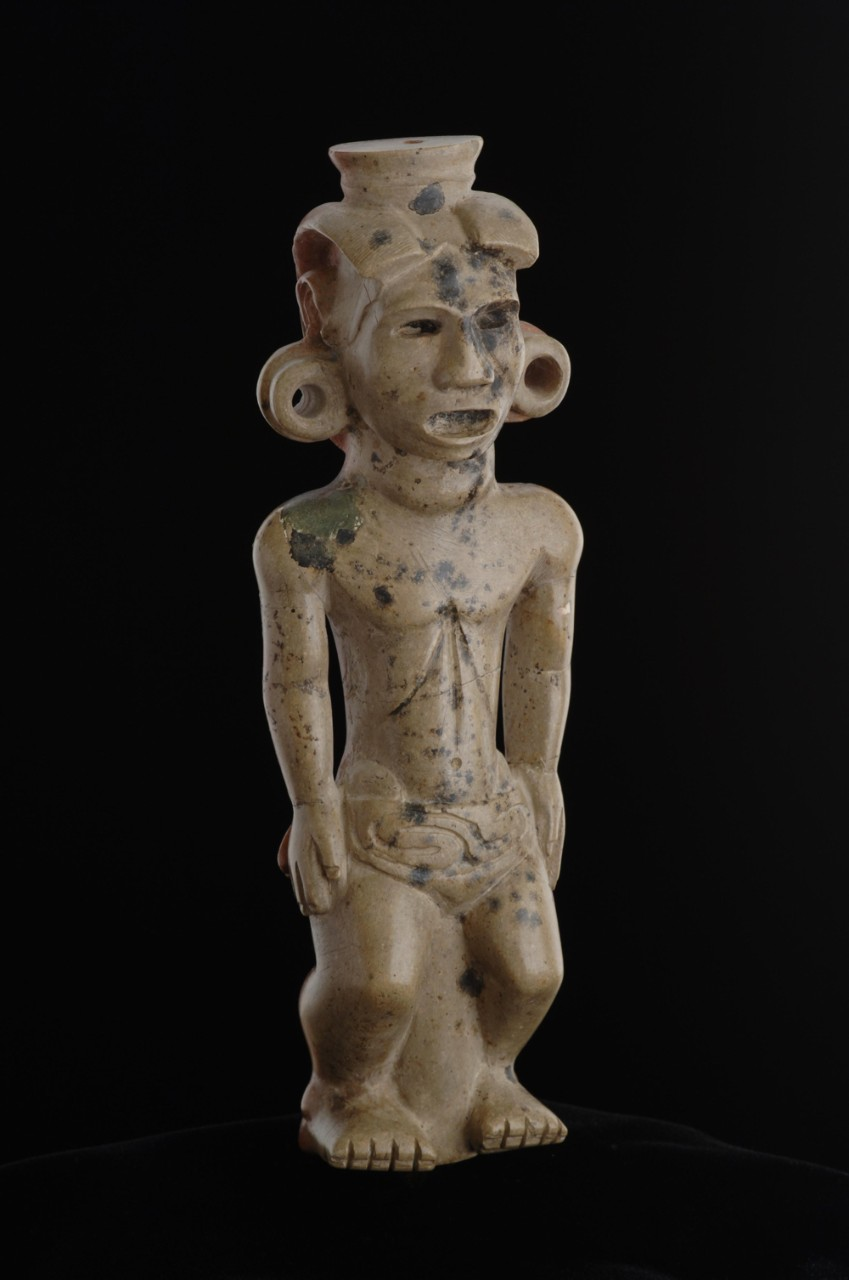 Front face and body of ancient carved tobacco pipe sculpture.