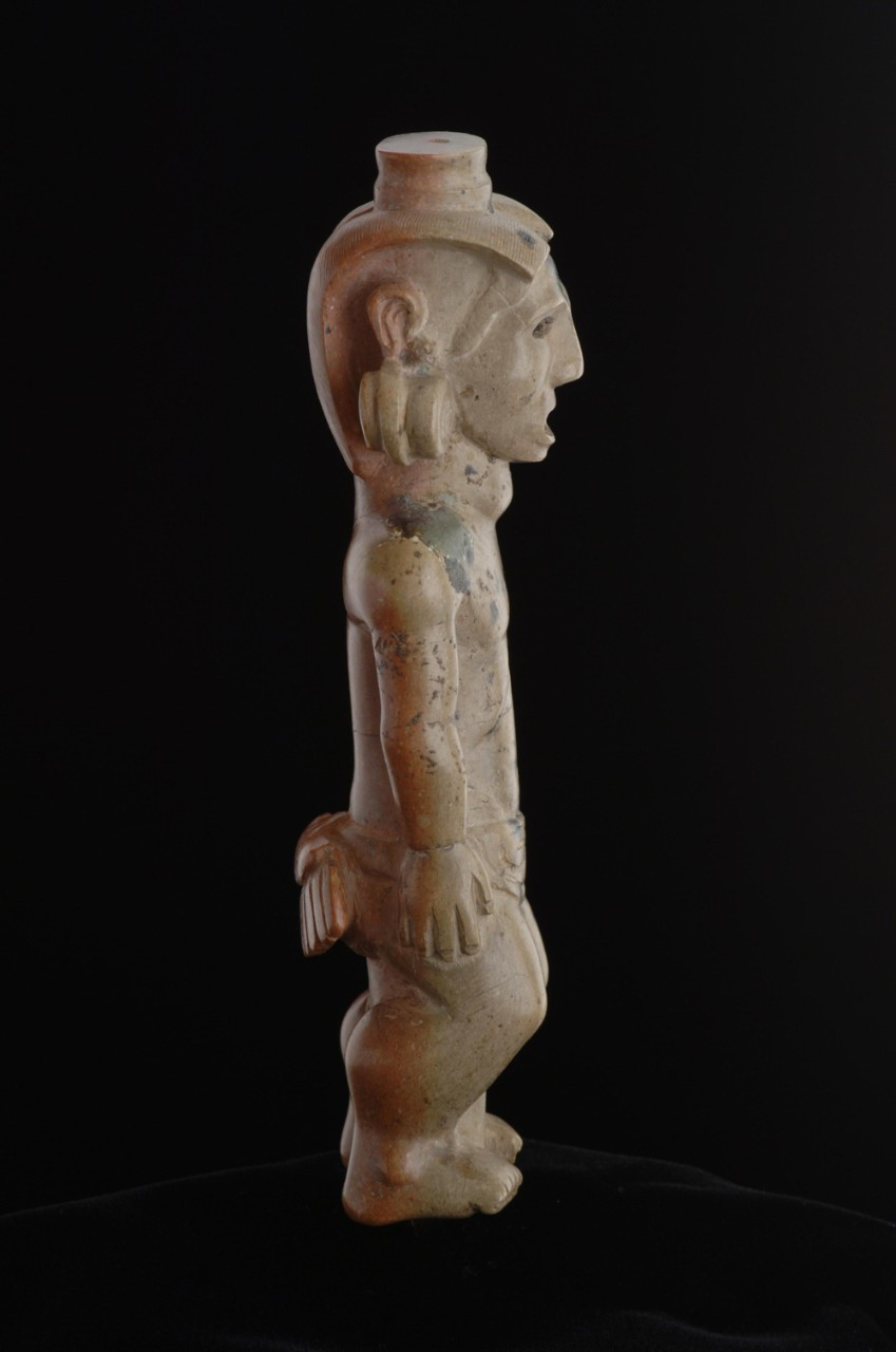 Profile of ancient tobacco pipe sculpture portraying a Native American wearing ceremonial regalia.