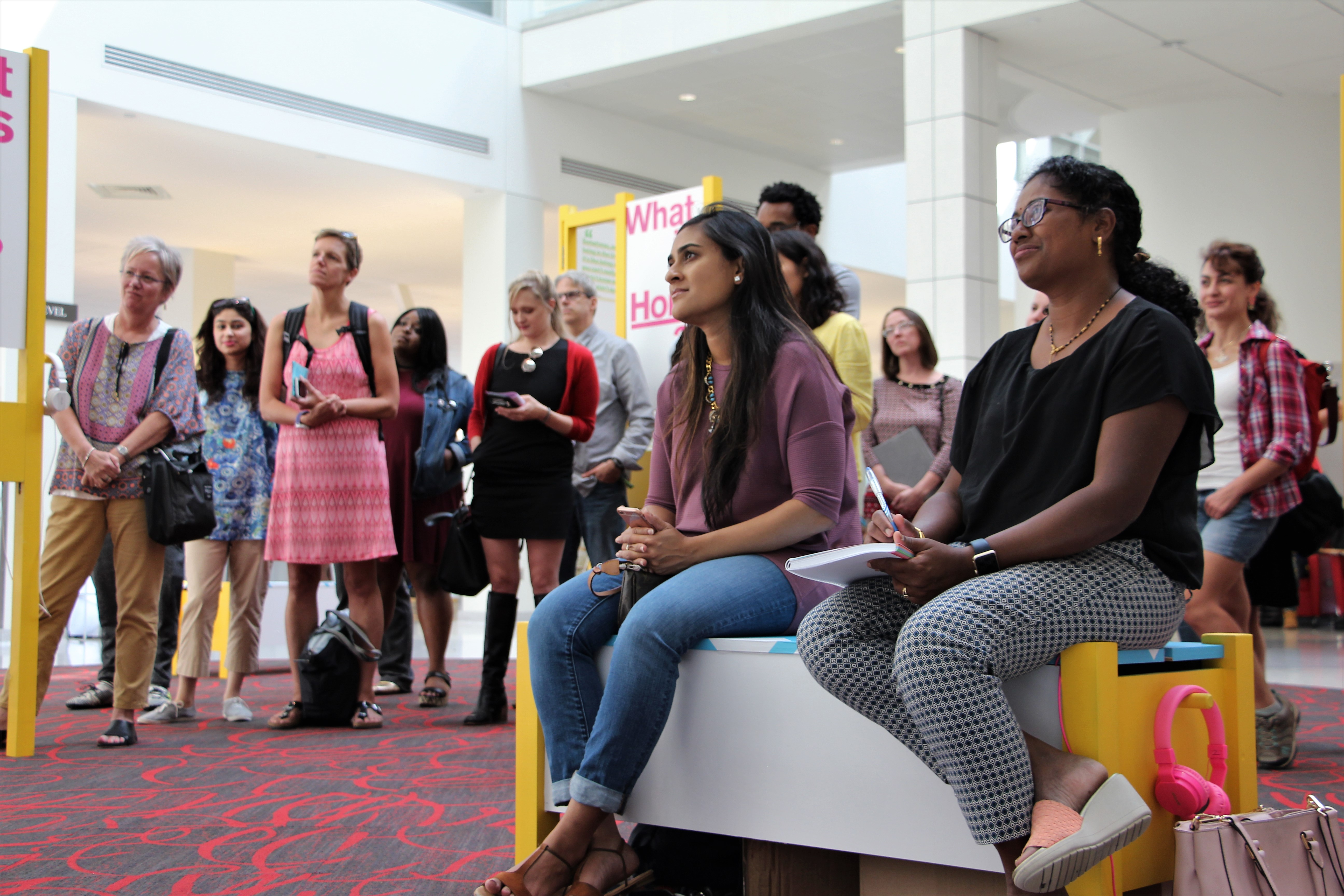 Exhibit attendees listening to the panel discussion in the Tangeman University Center atrium.