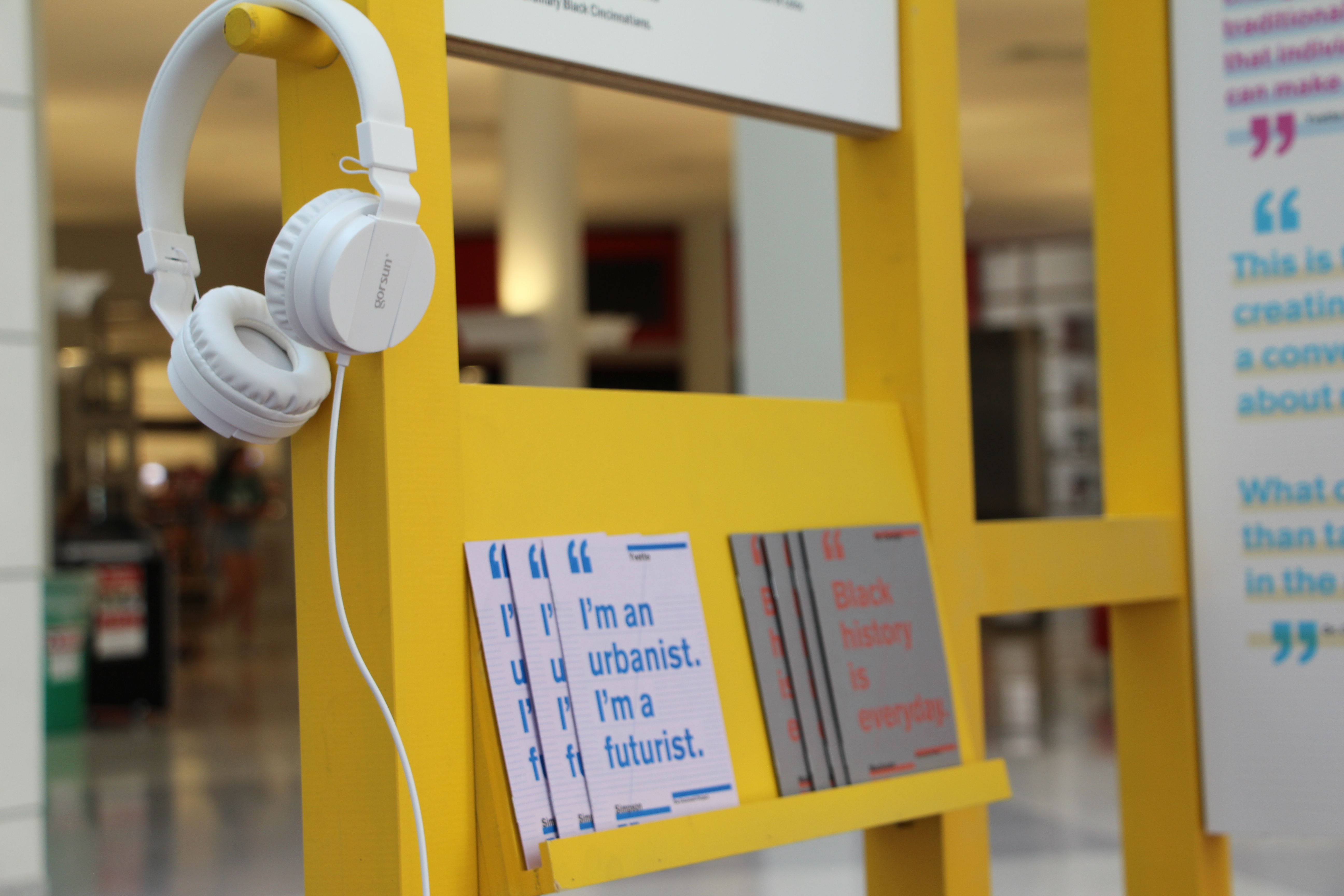 A pair of white headphones hangs from a bright yellow fixture, also holding a row of small paperback books