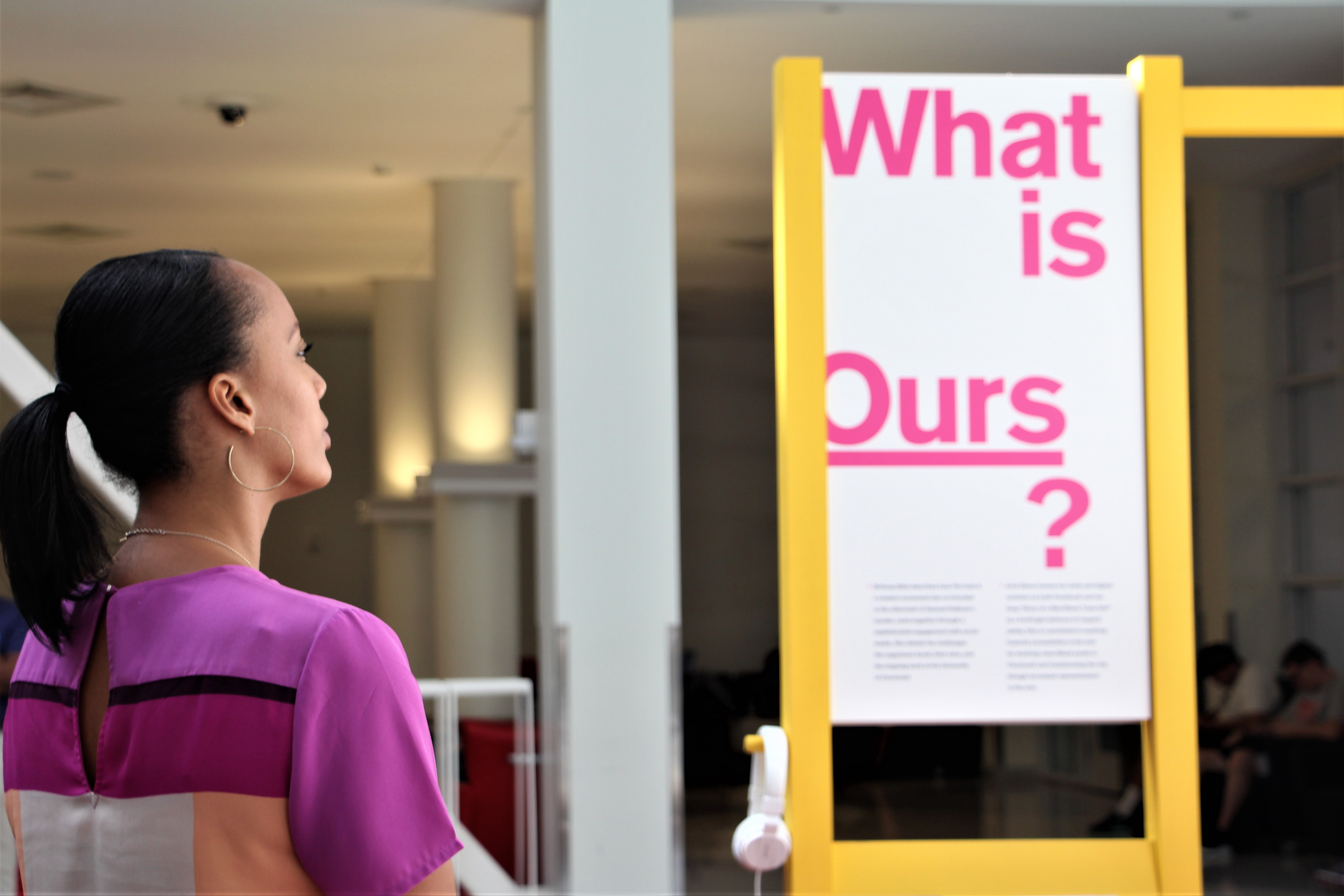 An exhibit attendee reads a panel filled with quotes that explore the question: What is ours?