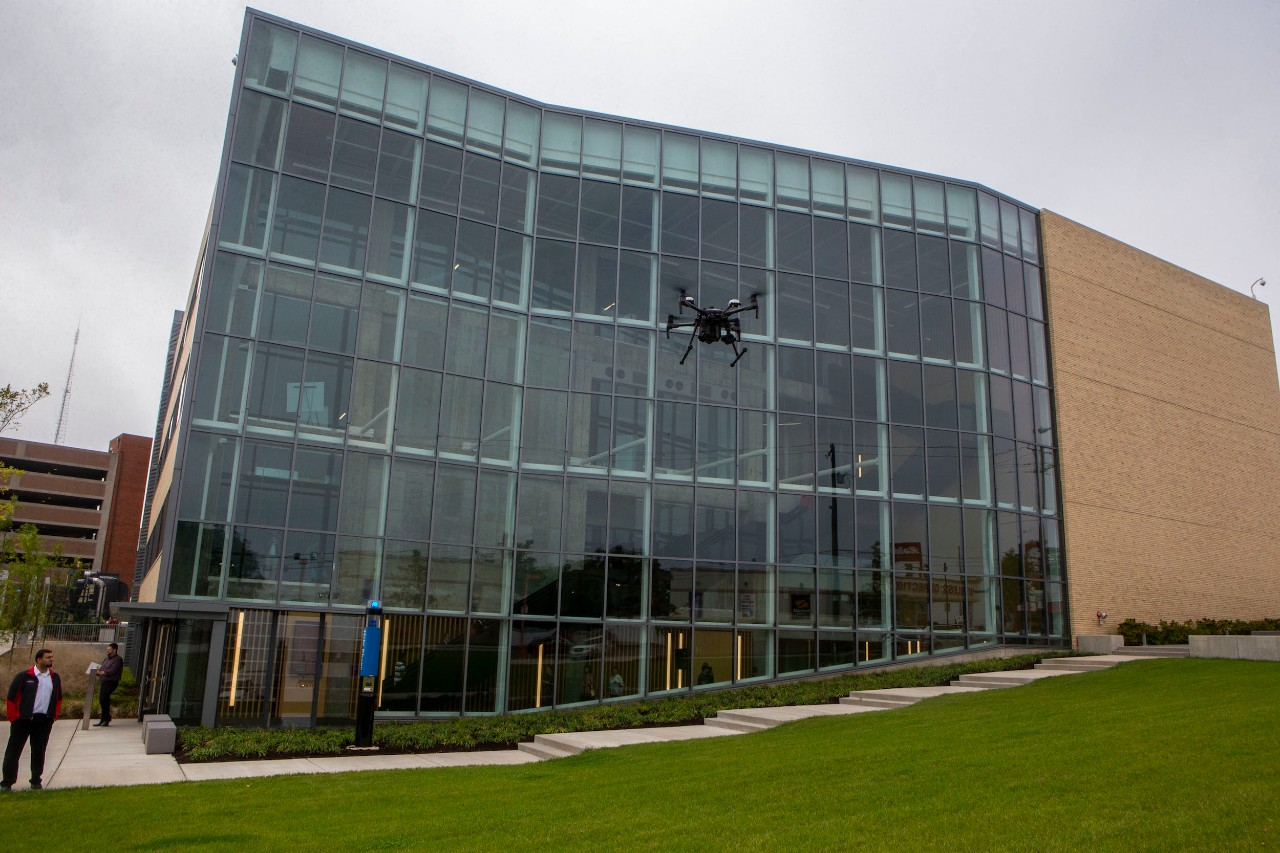 A drone flies outside of the 1819 innovation hub's glass atrium.