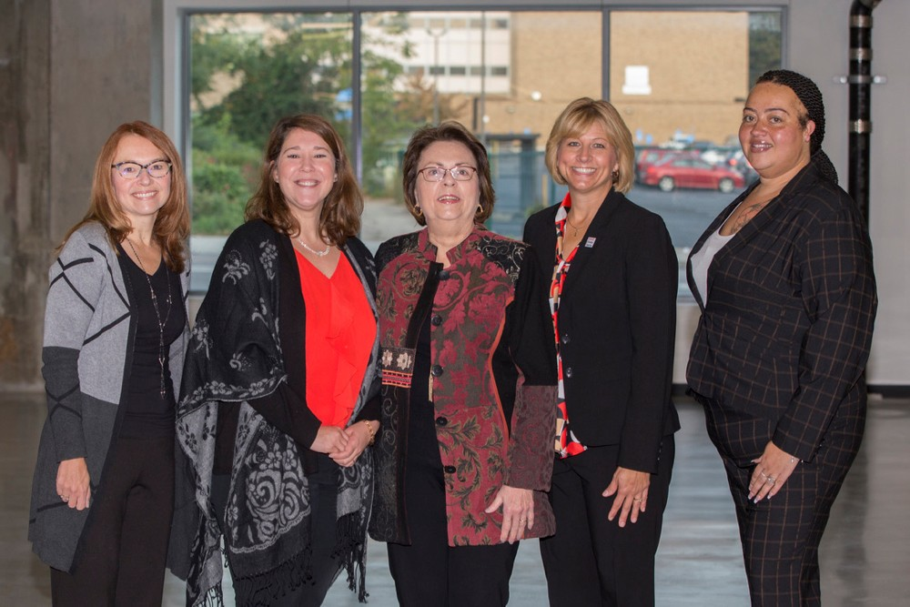 Five members of UC's Staff Senate stand together in UC's 1819 Hub.