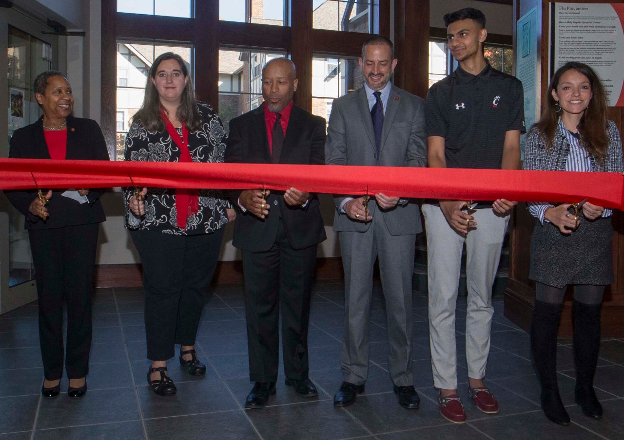 University leaders stand behind a giant red ribbon