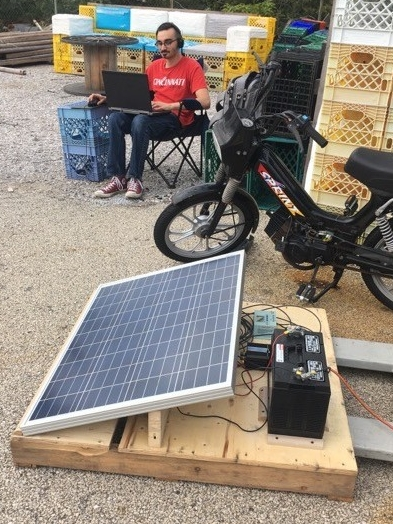 A man using a laptop sits outside by a solar panel